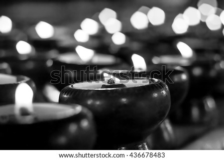 Light a candle in the dark, blur, black and white background. - stock photo