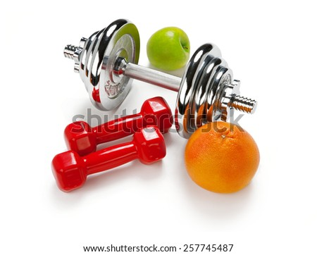 Light and Heavy dumbbells with green apple ang grapefruit / weight training equipment on white background    - stock photo