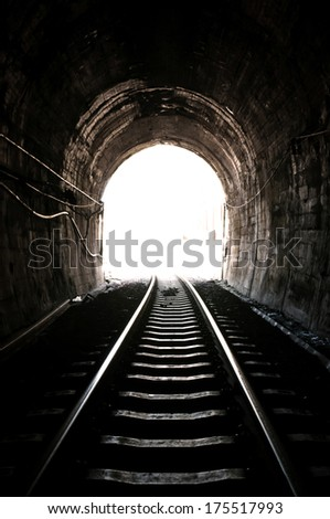 Light at the end of railroad tunnel - stock photo