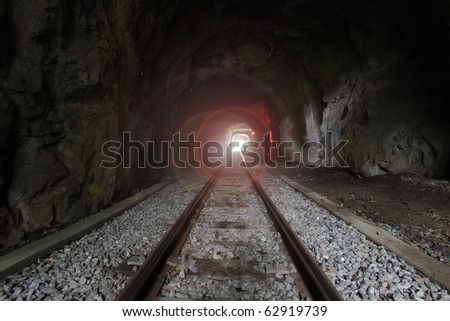 Light at the end of train tunnel - stock photo