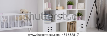 Light baby room with white cradle and new shelving unit - stock photo