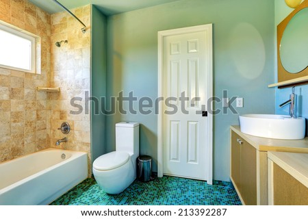 Light blue bathroom interior with modern vanity cabinet with vessel sink and tile wall trim - stock photo
