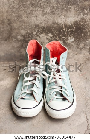 light blue canvas shoes on old concrete wall - stock photo