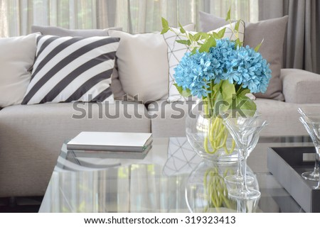 Light blue flower and wine glasses on center table with striped black and white pillow and gray tone pillows on beige sofa - stock photo