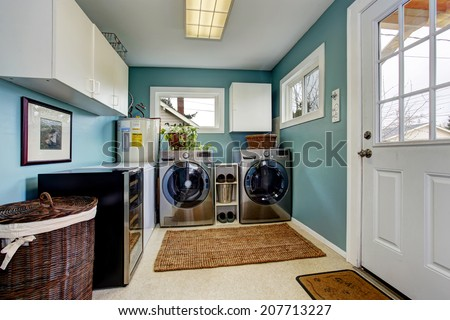 Light blue laundry room with modern steel appliances and white cabinets - stock photo