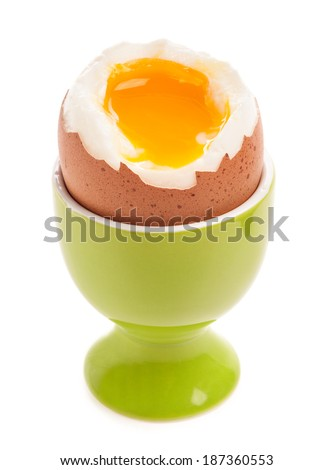 Light boiled egg in egg cup isolated on white - stock photo