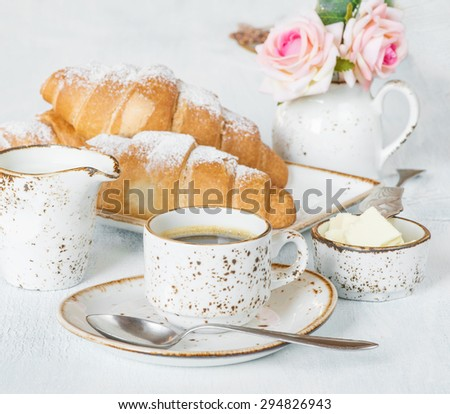 Light breakfast with a cup of coffee, croissants, cream and butter - stock photo