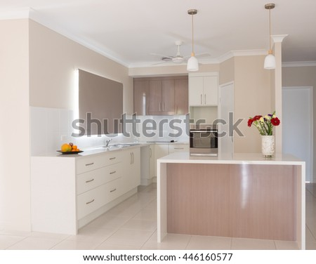 Light, bright new kitchen with island bench in new house - stock photo
