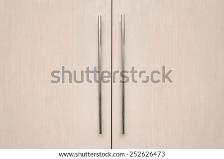 light brown doors with metal handles. - stock photo