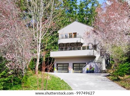 Light brown modern house exterior in spring forest with cherry blossom. - stock photo