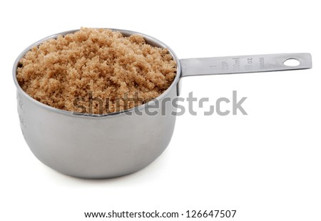 Light brown soft / muscovado sugar presented in an American metal cup measure, isolated on a white background - stock photo