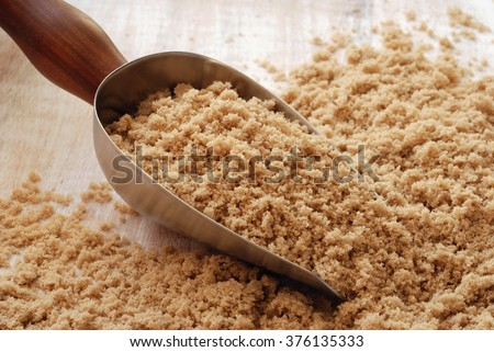 Light brown sugar spilling from vintage style, stainless steel scoop onto distressed wooden table.  Closeup with soft, natural lighting and shallow dof. - stock photo