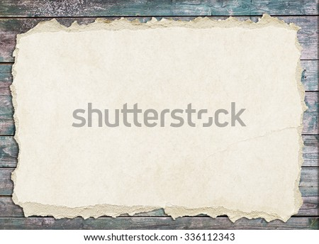 Light brown torn paper is on old wooden planks - stock photo