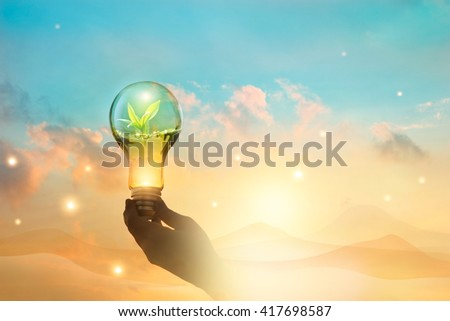 Light bulb against nature on desert mountain background. Ecological and energy concept  - stock photo
