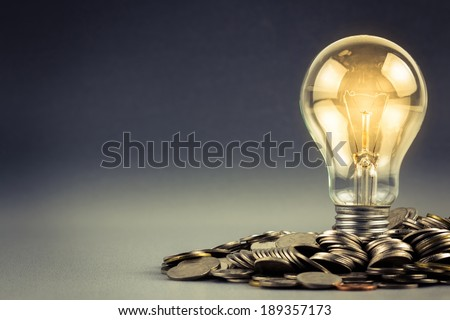 Light bulb and pile of coins with copy space - stock photo