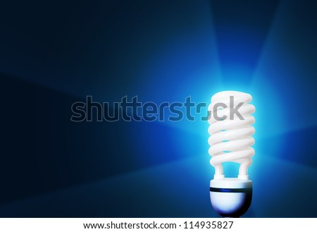 light bulb glowing on blue background - stock photo