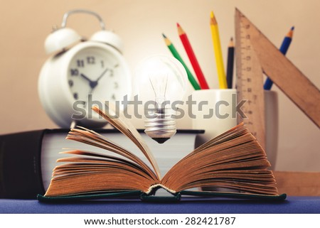 Light bulb glows brightly over an open book symbolizes the emergence of the idea  - stock photo