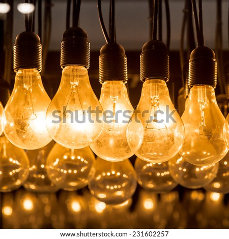 Light bulb,Hanging glowing light bulbs on black background,Lighting decor,chandeliers - stock photo