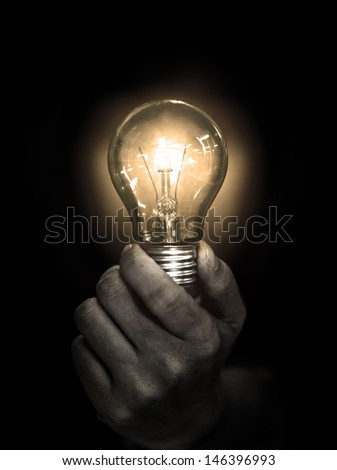 light bulb hold in hand on black background - stock photo