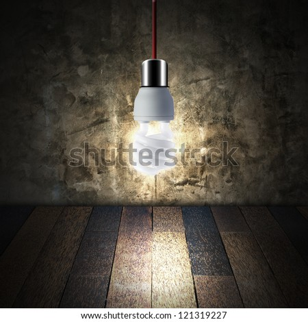 Light bulb in empty room with wooden floor and grunge wall. - stock photo