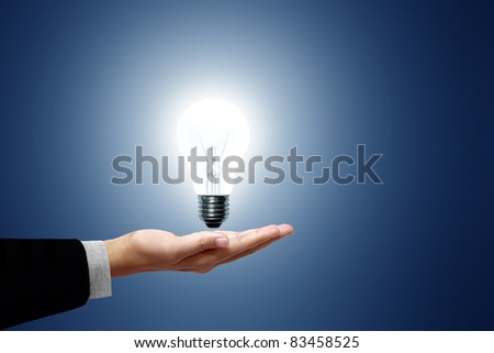 Light bulb in hand business woman on blue background - stock photo