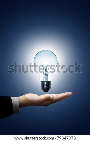 Light bulb in hand businessman - stock photo
