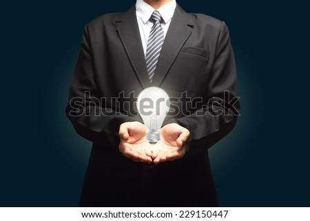 Light bulb in hand businessman on blue background. - stock photo