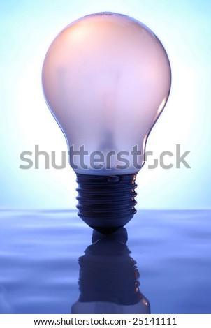 Light Bulb on blue, reflective surface. - stock photo
