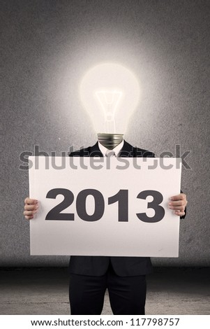 Light bulb person wearing business suit holding a 2013 billboard - stock photo