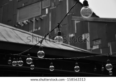 Light bulb string in black and white - stock photo