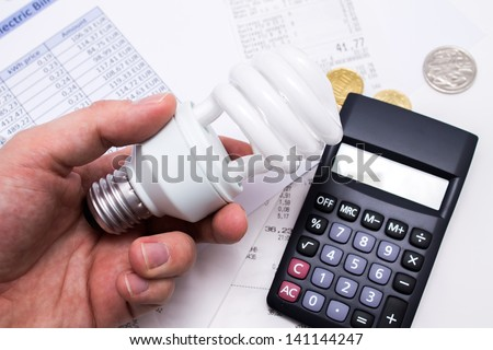 Light bulb whit calculator and coins - stock photo