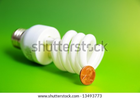light bulb with a penny, (energy costs), on green - stock photo