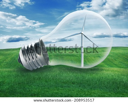 Light bulb with a wind turbine inside in green field. Environment, eco technology and energy concept. - stock photo