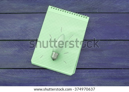 Light bulb with an idea in a notebook on a wooden table top with a blue tint - stock photo