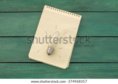 Light bulb with an idea in a notebook on a wooden table top with a turquoise hue - stock photo