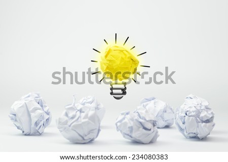 Light bulb with crumpled paper balls on white background - stock photo
