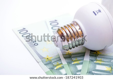 Light bulb with euro bill as a concept of saving energy - stock photo