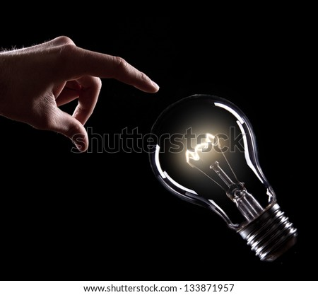 Light bulb with hand on black background - stock photo