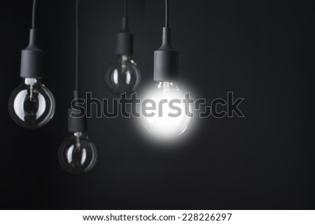 Light Bulb with One Light Turn On Hanging From Ceiling. - stock photo
