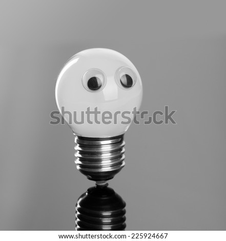 Light bulb with plastic eyes - stock photo