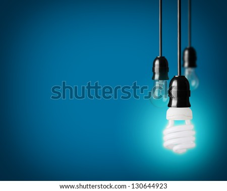 Light bulbs and energy saver bulb on blue background - stock photo