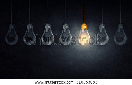 Light bulbs on dark background with one glowing - stock photo