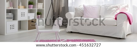 Light child room with white regale, sofa, rocking horse and pink carpet - stock photo