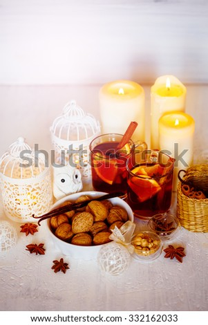 Light Christmas Decorations. Two Glasses with Mulled Wine, White Candles and Lantern, Toy Owl, Walnuts and Spices. Selective Focus, Shallow DOF. - stock photo