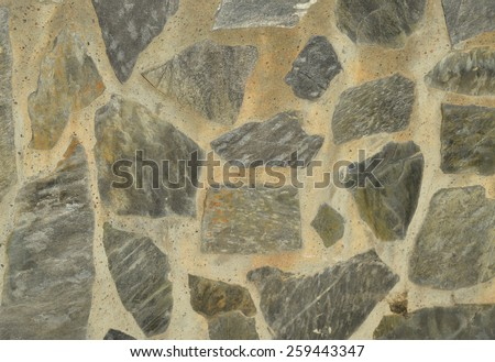 Light colored flagstone wall. Background photo. Random limestone pattern wall. Grey and yellow house wall. Pavement pattern. Flat stone elements. Old stones in random pattern. - stock photo