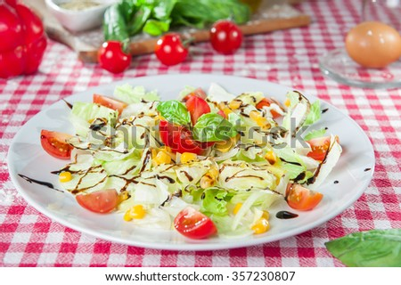 Light diet vegetable salad with Chinese cabbage, sweet corn, cherry tomatoes dressed with balsamic vinegar and olive oil on the  white plate on the kitchen tablecloth with different bright ingredients - stock photo