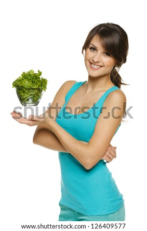 Light food concept. Smiling woman balancing lettuce leaves in transparent bowl, over white - stock photo