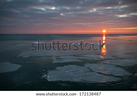 Light from a winter sunrise streaks across chunks of ice floating on the calm surface of Lake Michigan near Fort Sheridan, Illinois. - stock photo