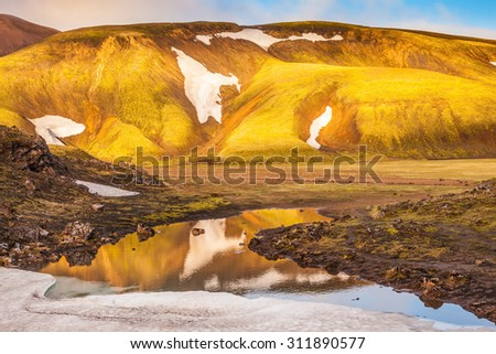 Light golden dawn illuminates the mountains and glaciers . The  sunrise in national park Landmannalaugar, Iceland - stock photo