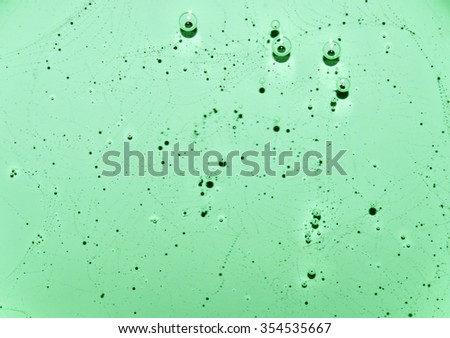 Light green fluid texture with patterns and bubbles. Light green water with bubbles. Closeup - stock photo